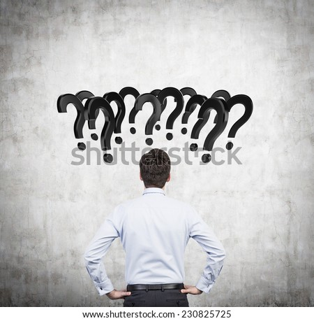 Businessmen is sitting in front of the whiteboard full of question marks.  - stock photo