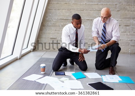 Businessmen Laying Documents On Floor To Plan Project - stock photo