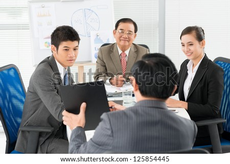Businessmen listening to their colleague attentively - stock photo