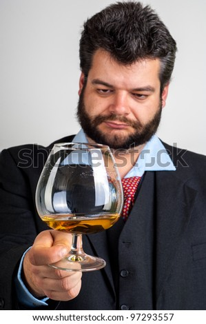 Businessmen looking at a glass of whiskey - stock photo