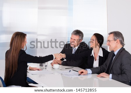 Businessmen Looking At Business Women Shaking Hand - stock photo