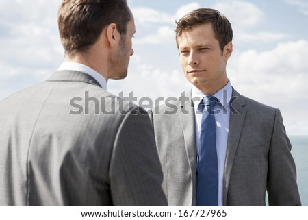 Businessmen looking at each other against sky - stock photo