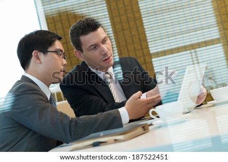 Businessmen looking at the screen of the laptop - stock photo