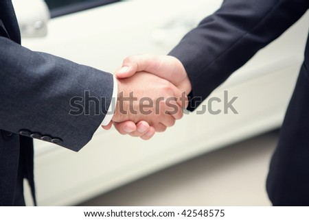 businessmen making handshake in front of a car