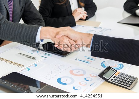 Businessmen making handshake in the meeting - stock photo