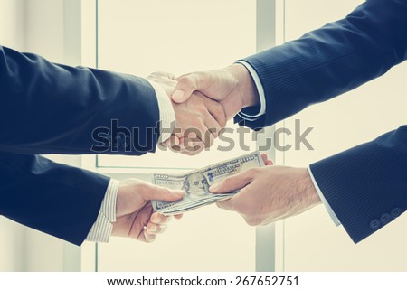 Businessmen making handshake while passing money, dealing & bribery concepts - vintage tone - stock photo