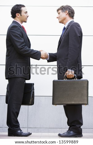 Businessmen meeting outside modern office