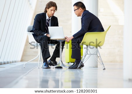 Businessmen Meeting With Laptop In Modern Office - stock photo