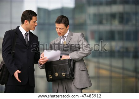 Businessmen negotiating in front of a building