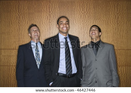 Businessmen of ethnic diversity standing together smiling and laughing. Horizontal shot. - stock photo
