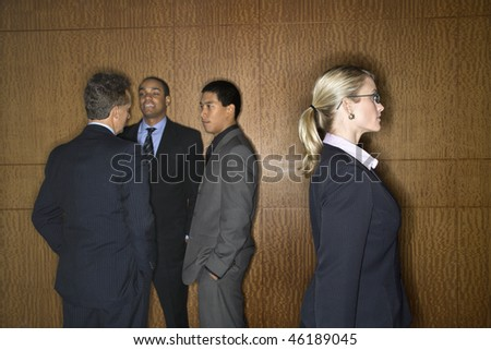 Businessmen of ethnic diversity talk in a group as a Caucasian businesswoman walks by. Horizontal shot. - stock photo