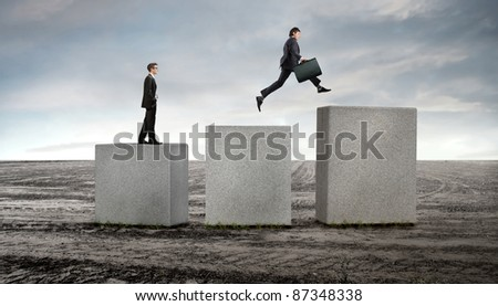 Businessmen on stone cubes advancing on higher ones - stock photo
