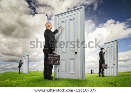 Businessmen or salesmen with briefcases knocking at several doors in a green field - stock photo