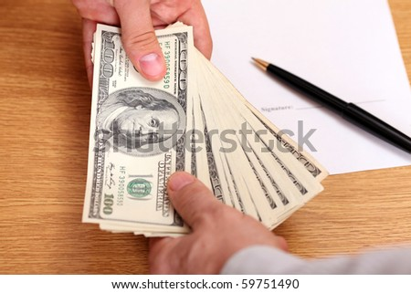 Businessmen passing money with contract on the background - stock photo