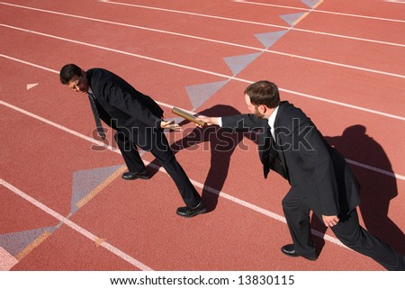 Businessmen passing the baton in a track relay - stock photo