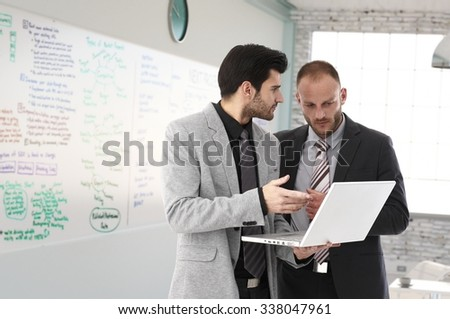 Businessmen planning, looking at laptop at office in front of a huge whiteboard.
