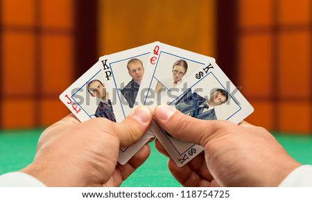 Businessmen playing poker with business team cards - stock photo