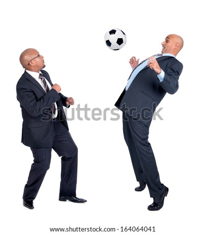 Businessmen playing soccer ball isolated in white - stock photo