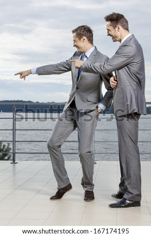 Businessmen pointing at something against sky - stock photo