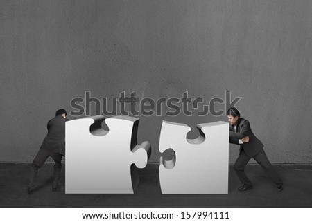 Businessmen push two heavy puzzles together in concrete wall background. - stock photo