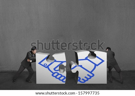 Businessmen push two heavy puzzles together with shake hand drawing in concrete wall background. - stock photo