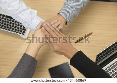 businessmen put their hand together for use as unity, cooperation and teamwork concept - stock photo