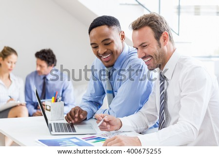 Businessmen reviewing a statistical report at desk in office - stock photo