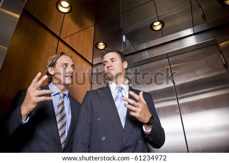 Businessmen riding in elevator conversing - stock photo