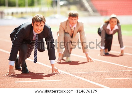 Businessmen running on track racing at athletich stadium - stock photo