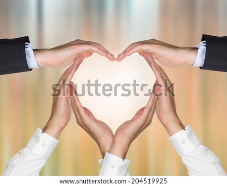 Businessmen's hands form a heart symbol as a metaphor of client relationships. - stock photo