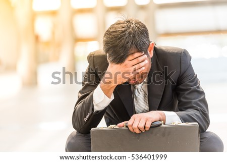 Businessmen sad worry tired sit with black bag on street