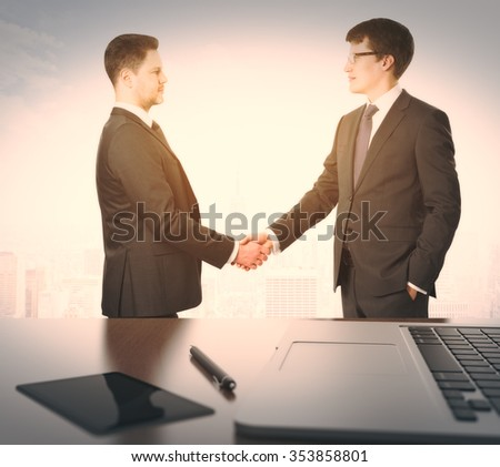 Businessmen shake hands and table withlaptop and digital tablet