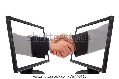 Businessmen shake hands from two lcd monitors - stock photo