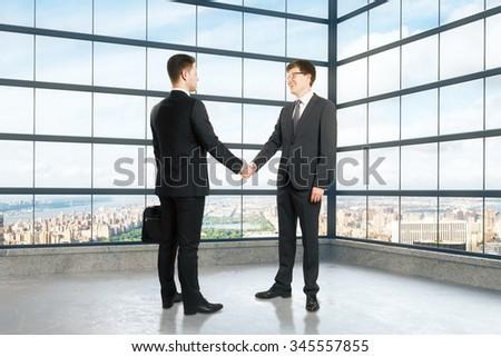 Businessmen shake hands in empty loft room  3D Render - stock photo
