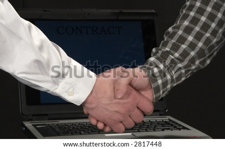 Businessmen shaking hand in front of a laptop