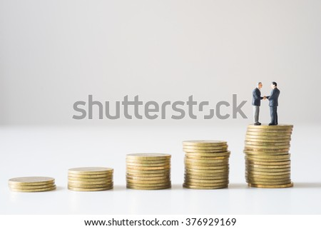 Businessmen shaking hand over coins stacks. Investment concept.