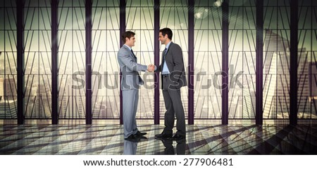 Businessmen shaking hands against room with large window looking on city - stock photo
