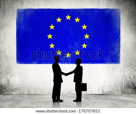 Businessmen Shaking Hands at European Union Flag - stock photo