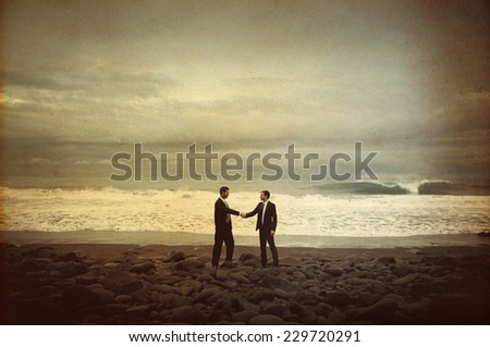 Businessmen Shaking Hands by the Beach - stock photo