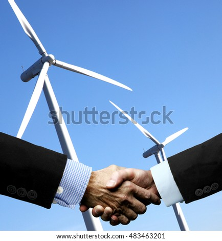 Businessmen shaking hands in front of Windpower Station on the blue Sky