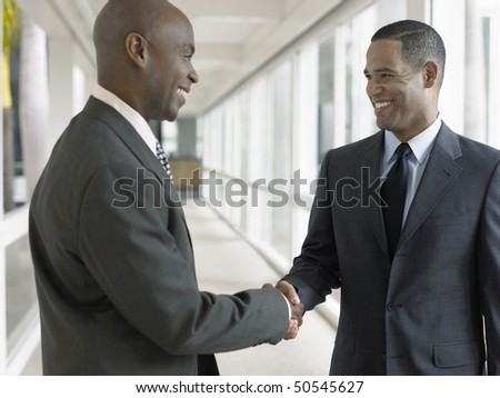 Businessmen shaking hands in hallway - stock photo