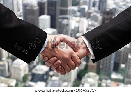 businessmen shaking hands on background of city - stock photo