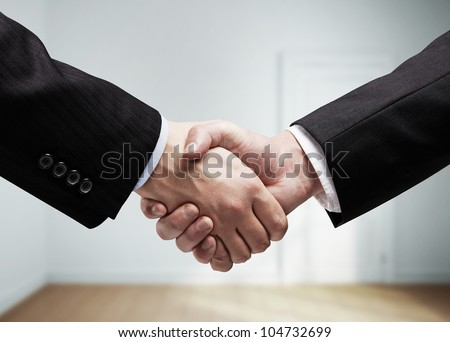 businessmen shaking hands on background of white room - stock photo
