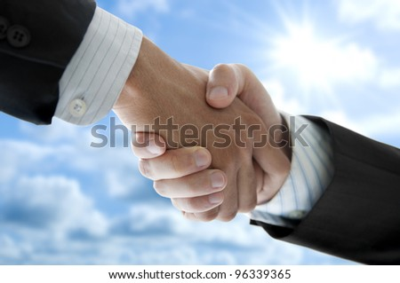 Businessmen shaking hands over blue sky, low angle view. - stock photo