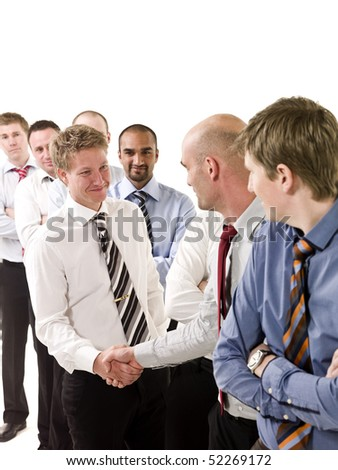 Businessmen shaking hands standing in a group