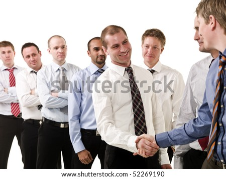 Businessmen shaking hands standing in a group of people