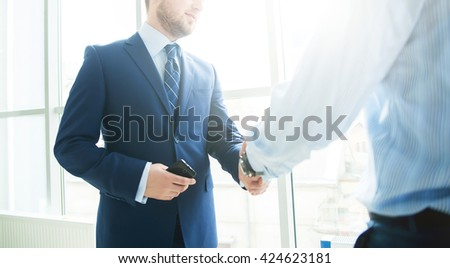 Businessmen shaking hands. Two confident businessmen shaking hands and smiling while standing