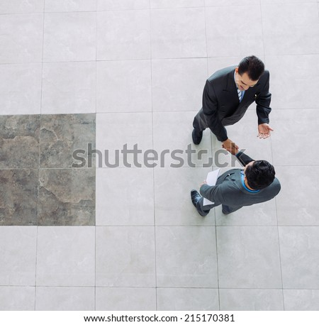 Businessmen shaking hands, view from the top - stock photo