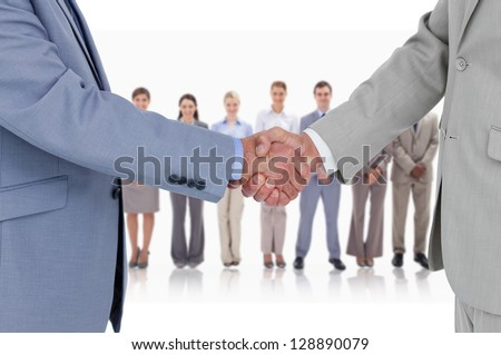 Businessmen shaking hands with business team standing behind