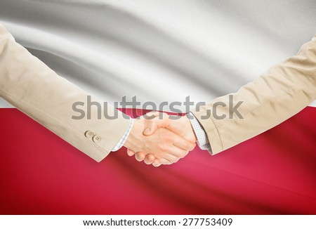 Businessmen shaking hands with flag on background - Poland - stock photo
